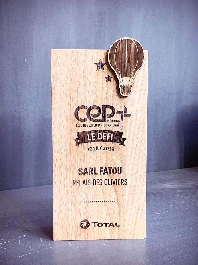 Trophées récompenses en bois chêne massif avec un empiècement en chêne gravés par laser CEP pour agence I-Communication et Total