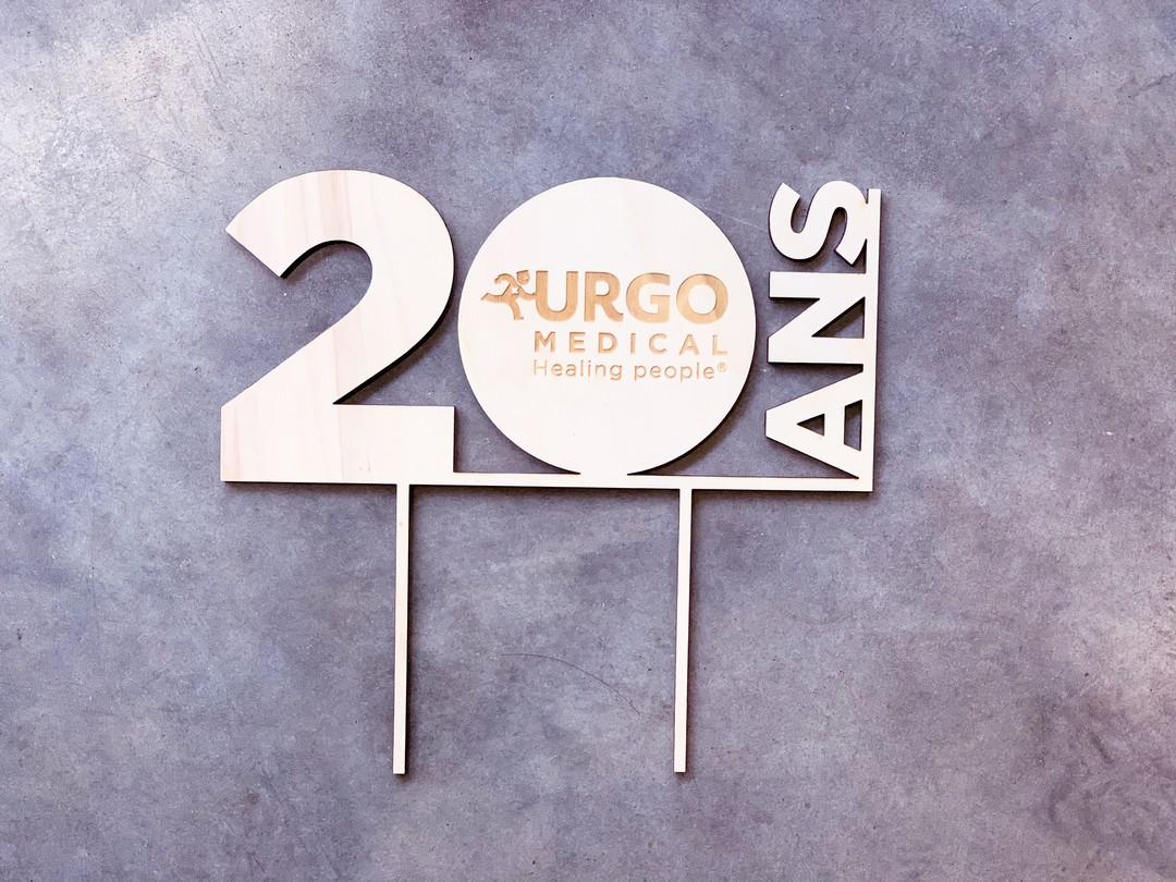 Cake topper en peuplier gravé sur mesure par laser pour les laboratoires Urgo et agence séline décoration