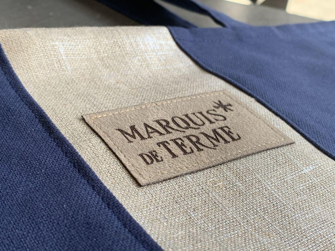 Etiquettes en suédine cuir gravé par laser produits dérivés pour le chateau marquis de terme sur des sacs conçus par Agathe and co