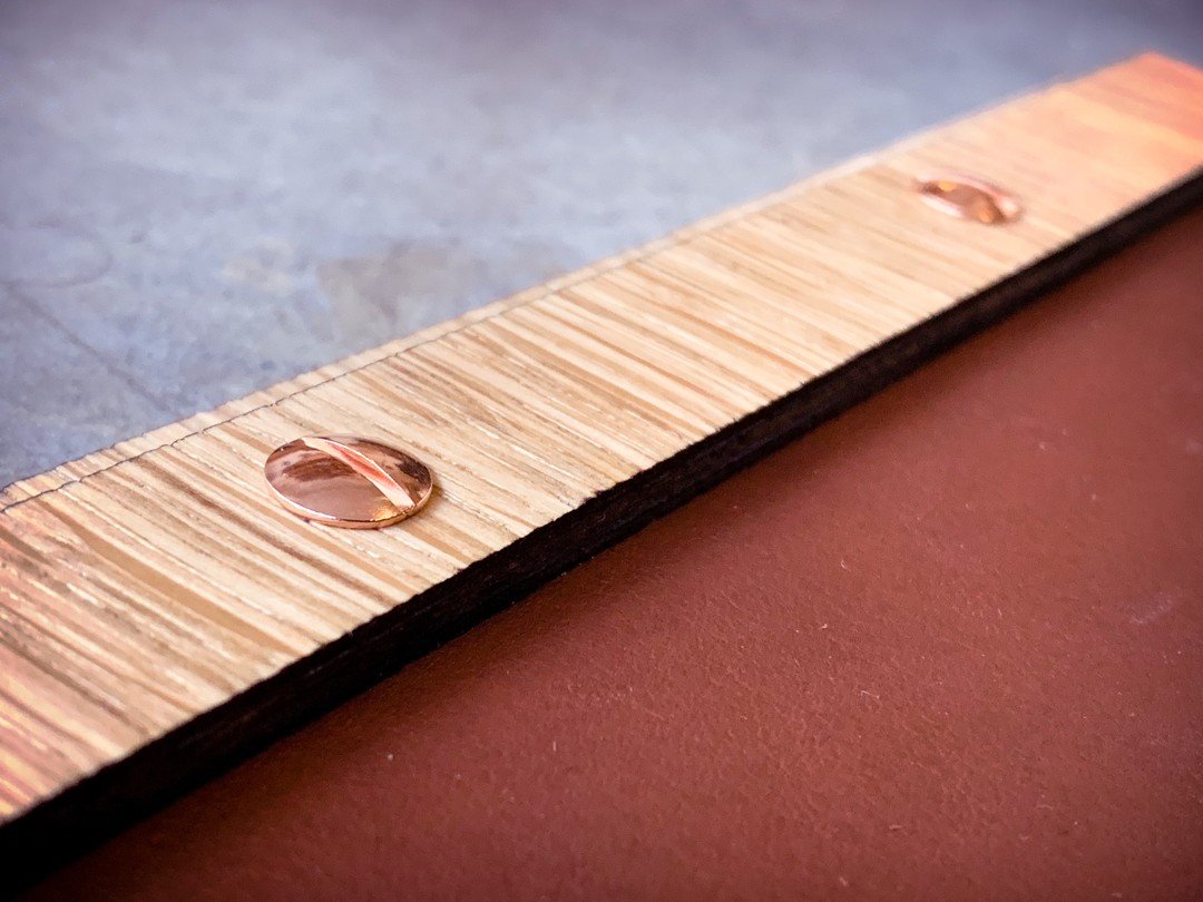 Carte porte menus sur mesure sur chêne et cuir gravé et découpé par laser pour le restaurant monzu à bordeaux vis de reliure en laiton